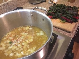 The broth comes to a boil while the chard waits for its turn in the pot.